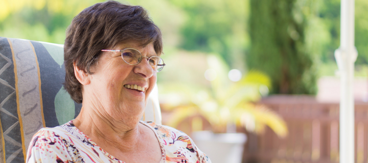 Older woman sitting outside smiling consumer directed care