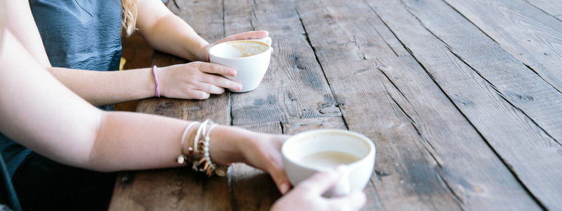 Hands of two women holding coffees while sitting at wooden table