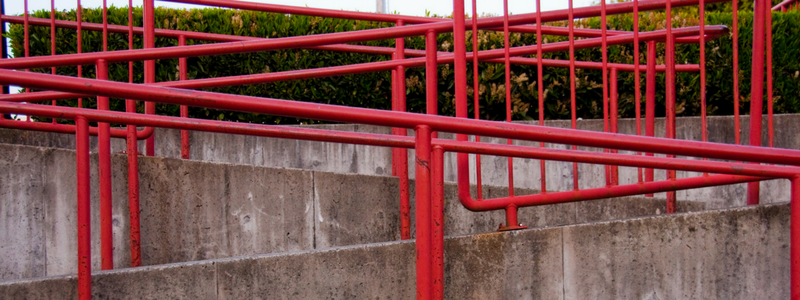 Concrete accessibility ramp with red railings